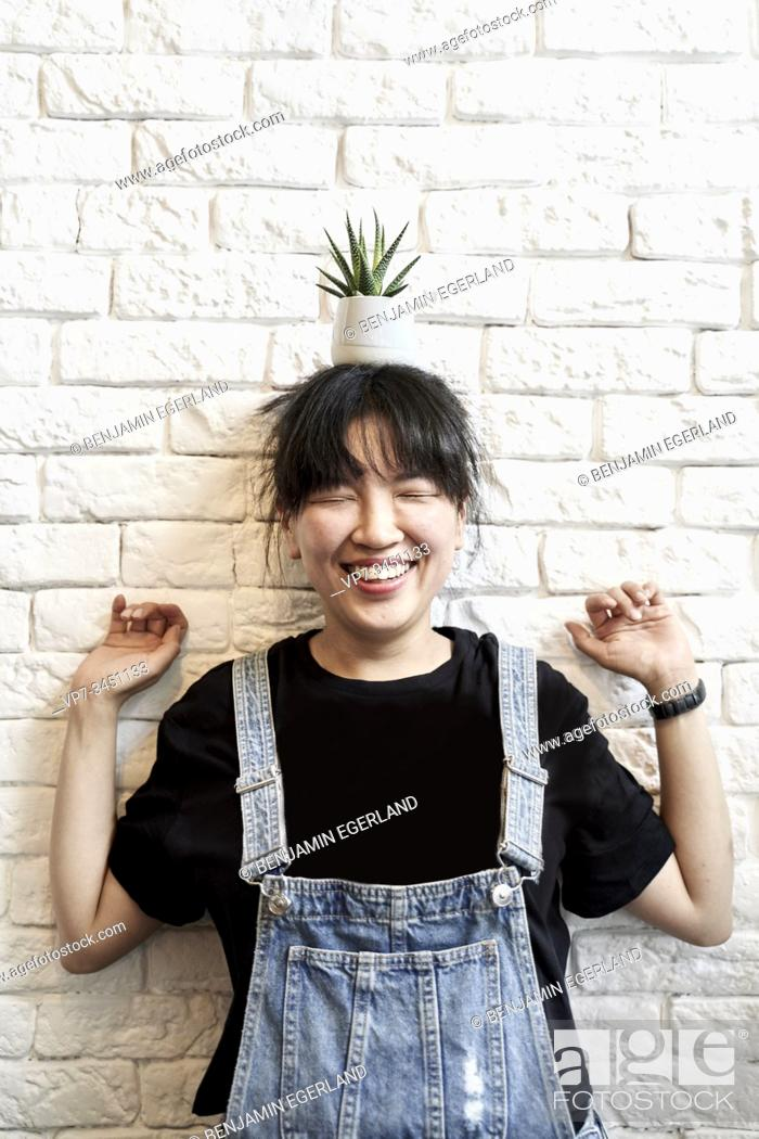 Stock Photo: Korean woman holding a cup with leaves on her head.