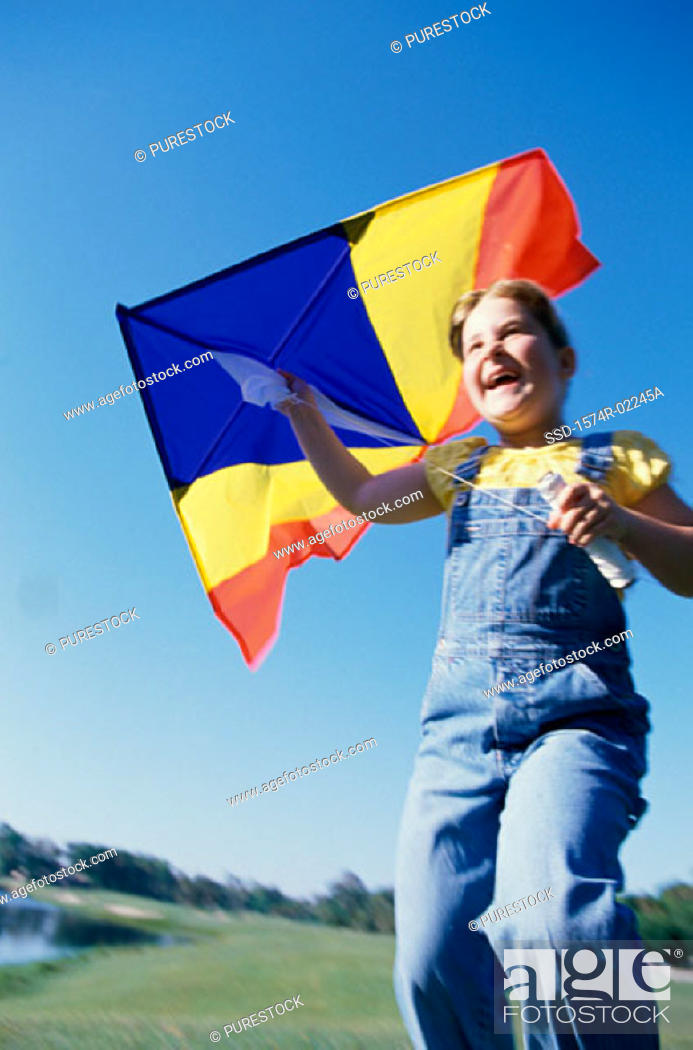 Stock Photo: Low angle view of a girl holding a kite.