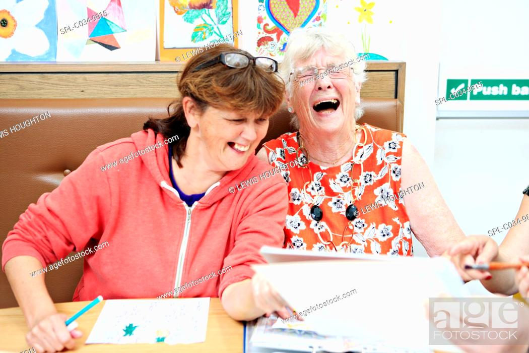 Stock Photo: MODEL RELEASED. Dementia art therapy participants. Woman with dementia (right) and a community worker (left) at an art therapy group.