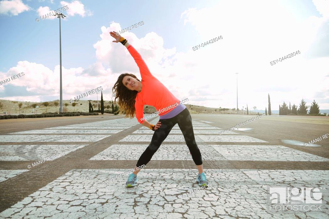 Imagen: young woman stretching before running with a orange shirt.
