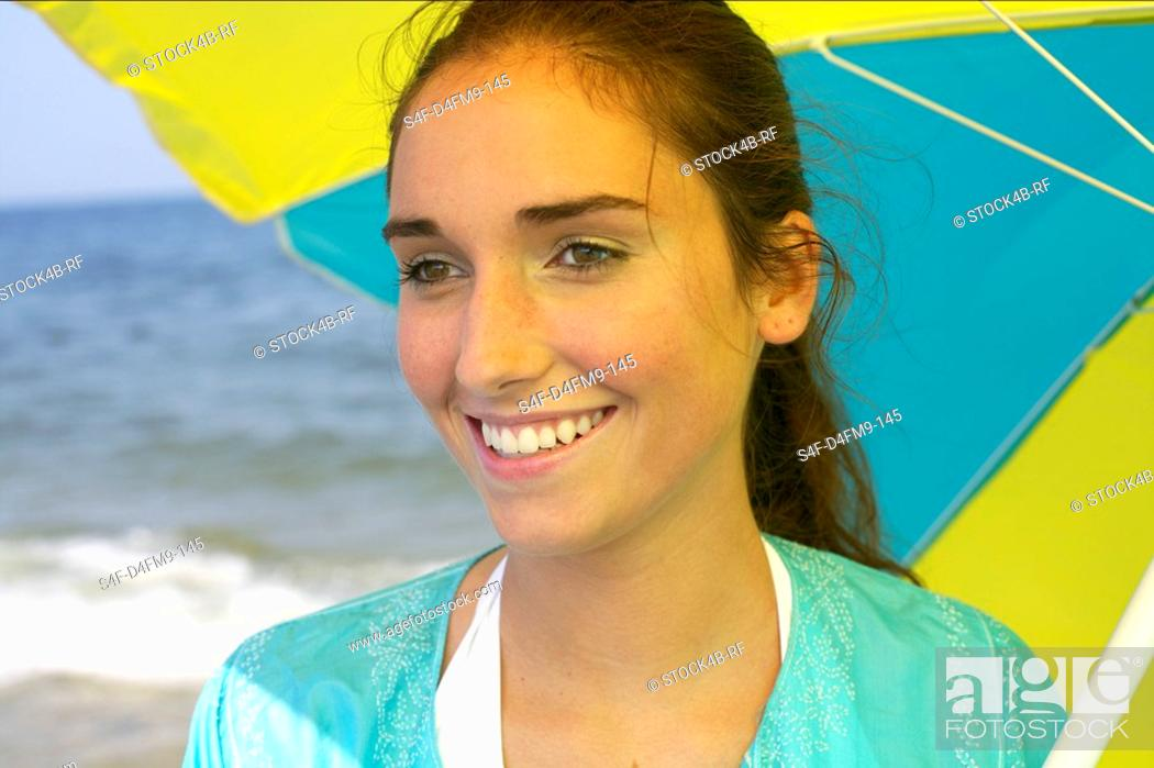 Stock Photo: Young brunette woman under an umbrella at the beach, close-up.