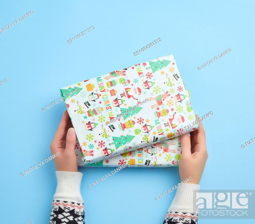 Stock Photo: two female hands hold a paper closed box on a blue background. Festive concept.