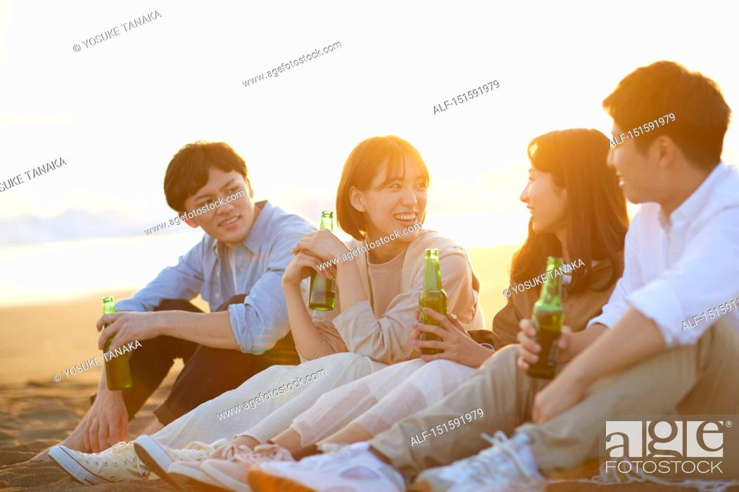 Stock Photo: Young Japanese friends at the beach.