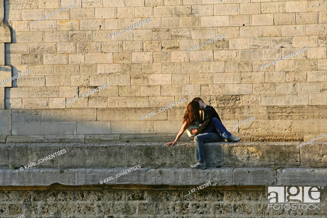 Stock Photo: Young couple kissing on the quay wall of the Seine, Paris, France, Europe.