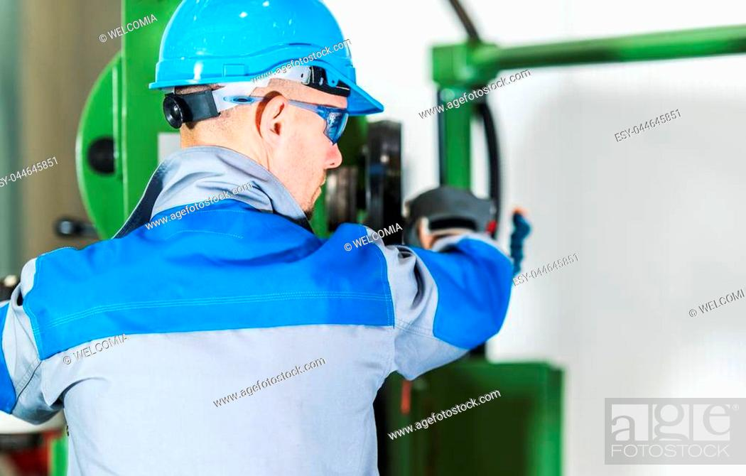 Stock Photo: Professional Heavy Duty Machinery Operator. Caucasian Metalworking Industry Worker in Blue Hard Hat in Front of Machine Console. Industrial Theme.