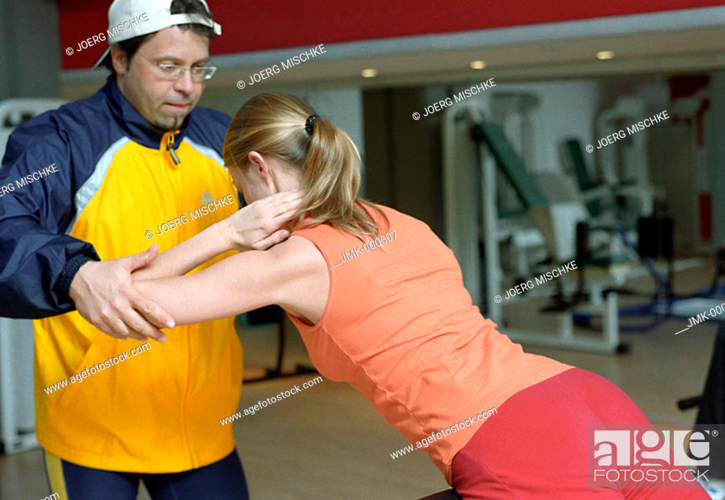 Stock Photo: Young woman at the gym, fitness center, doing exercises at an athletic implement, instructed by a coach, trainer.
