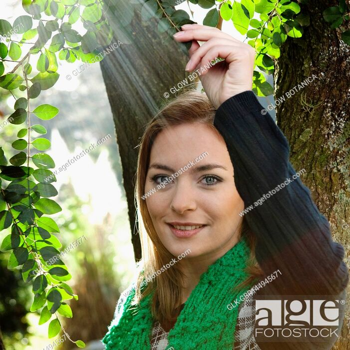 Stock Photo: Portrait of a woman holding a branch and smiling.