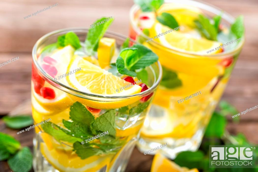 Stock Photo: Lemon mojito cocktail with mint and pomegranate, cold refreshing drink or beverage.