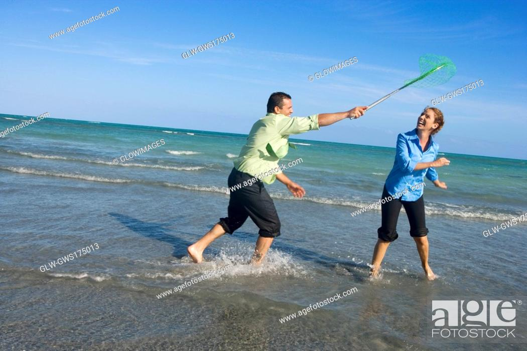 Stock Photo: Mid adult man holding a fishing net over a mid adult woman on the beach.