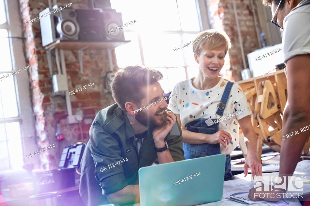 Stock Photo: Smiling designers meeting at laptop in workshop.