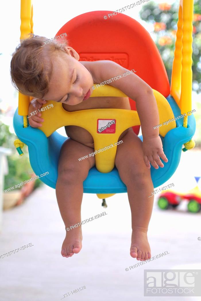 Stock Photo: Baby boy fast asleep on a swing.