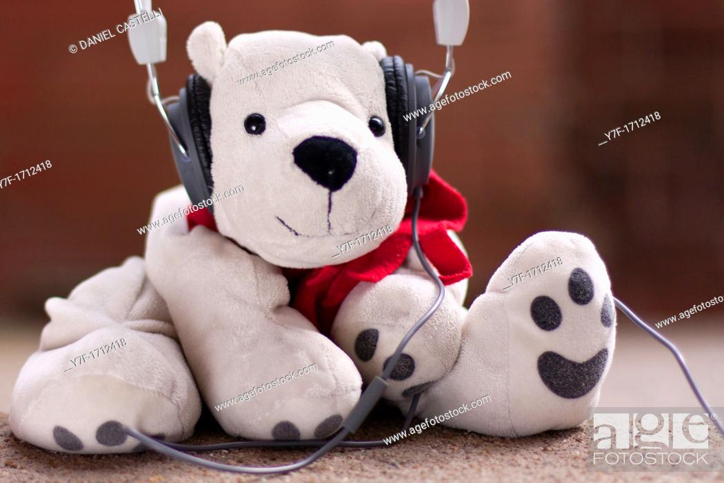 Stock Photo: White teddy bear listening to music with headphones.