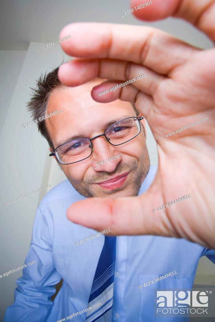 Stock Photo: Business man trying to fix a webcam.