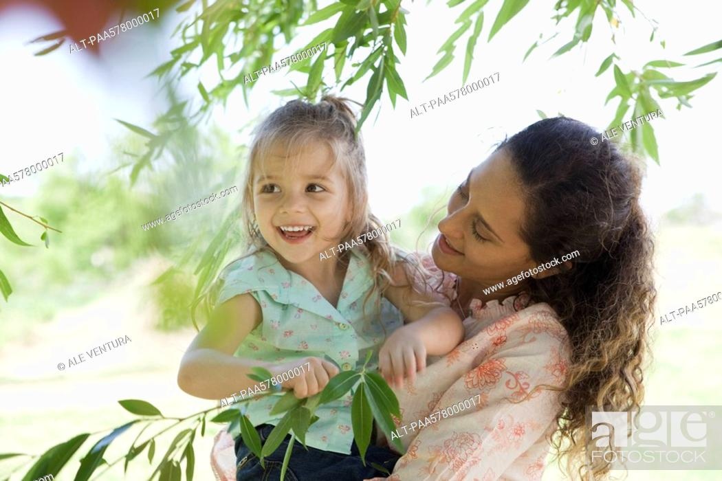 Stock Photo: Mother holding young daughter outdoors, girl holding onto tree branch.