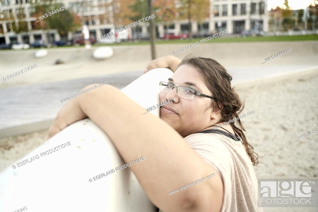 Imagen: woman leaning on wall in park.