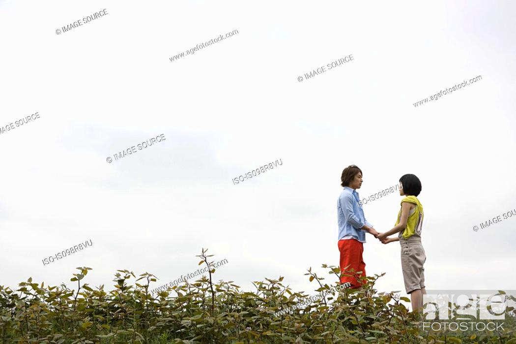 Stock Photo: Young couple holding hands outdoors.