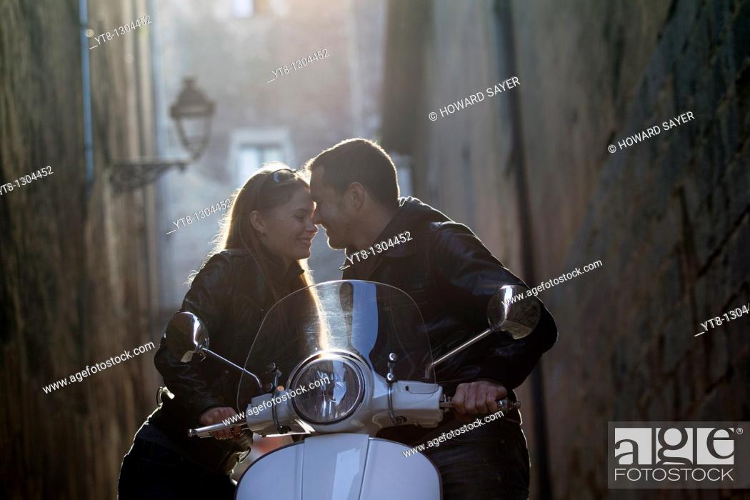 Stock Photo: Couple embracing and leaning on a motor scooter.