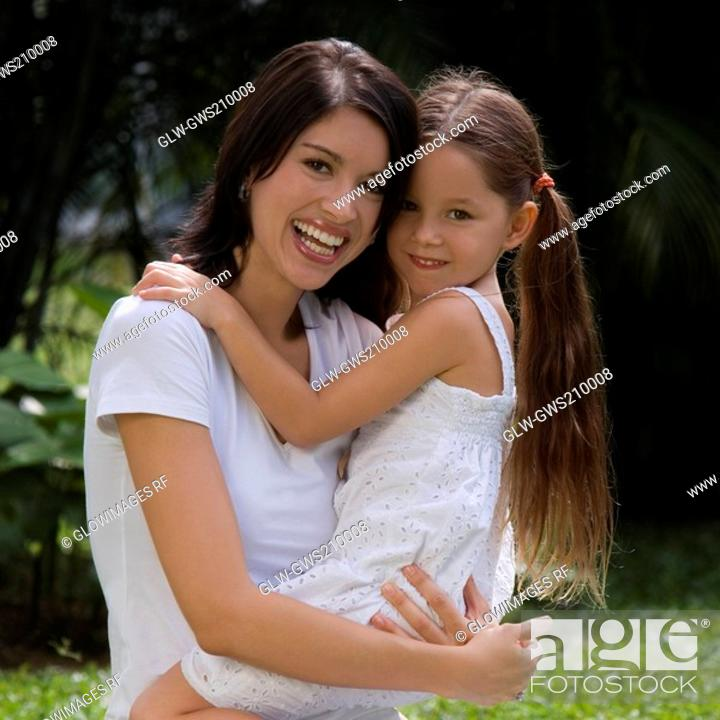 Stock Photo: Portrait of a young woman carrying her daughter and smiling.