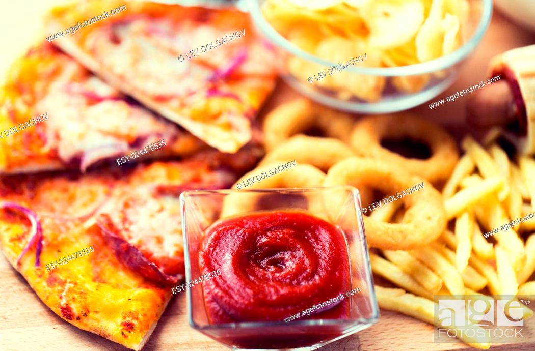 Stock Photo: fast food and unhealthy eating concept - close up of ketchup in glass bowl over pizza, deep-fried squid rings, potato chips, peanuts and ketchup on wooden table.