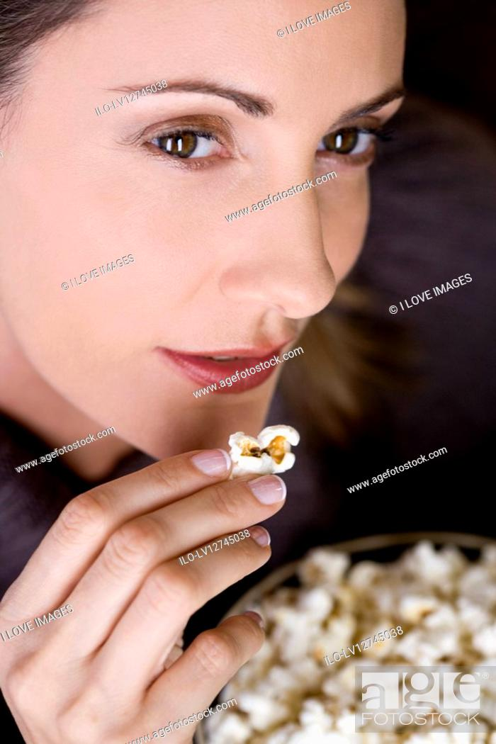 Stock Photo: Close-up of a mid adult woman eating popcorn.