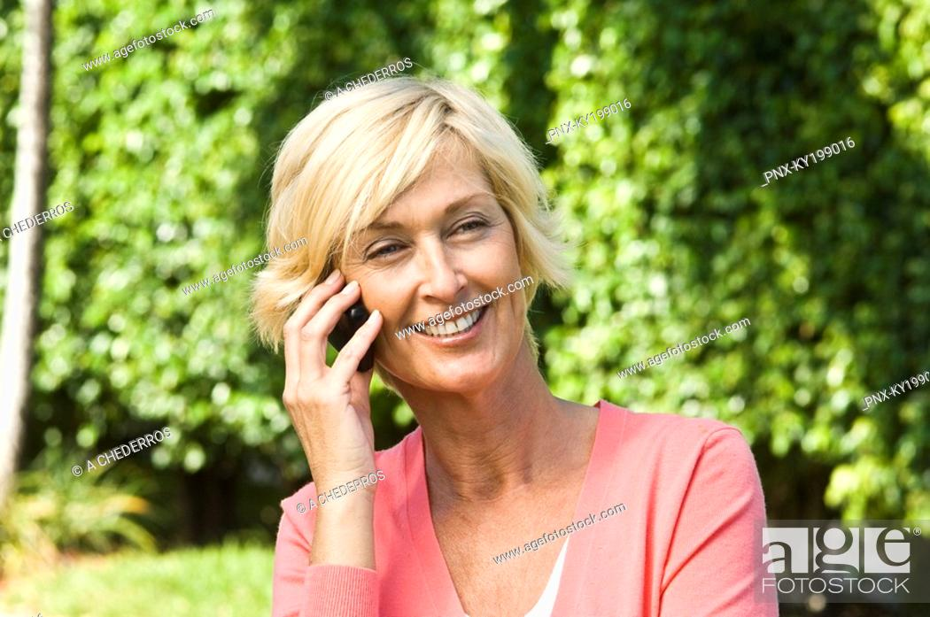 Stock Photo: Woman talking on a mobile phone and smiling.