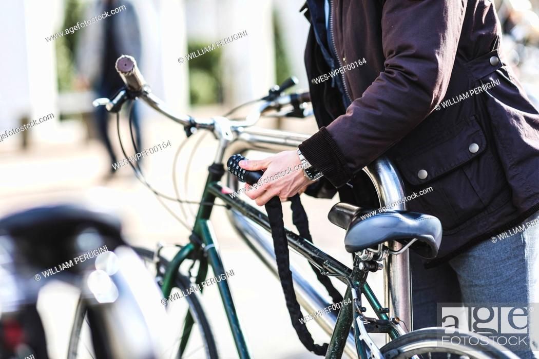 Photo de stock: Businessman locking bicycle in the city, partial view.