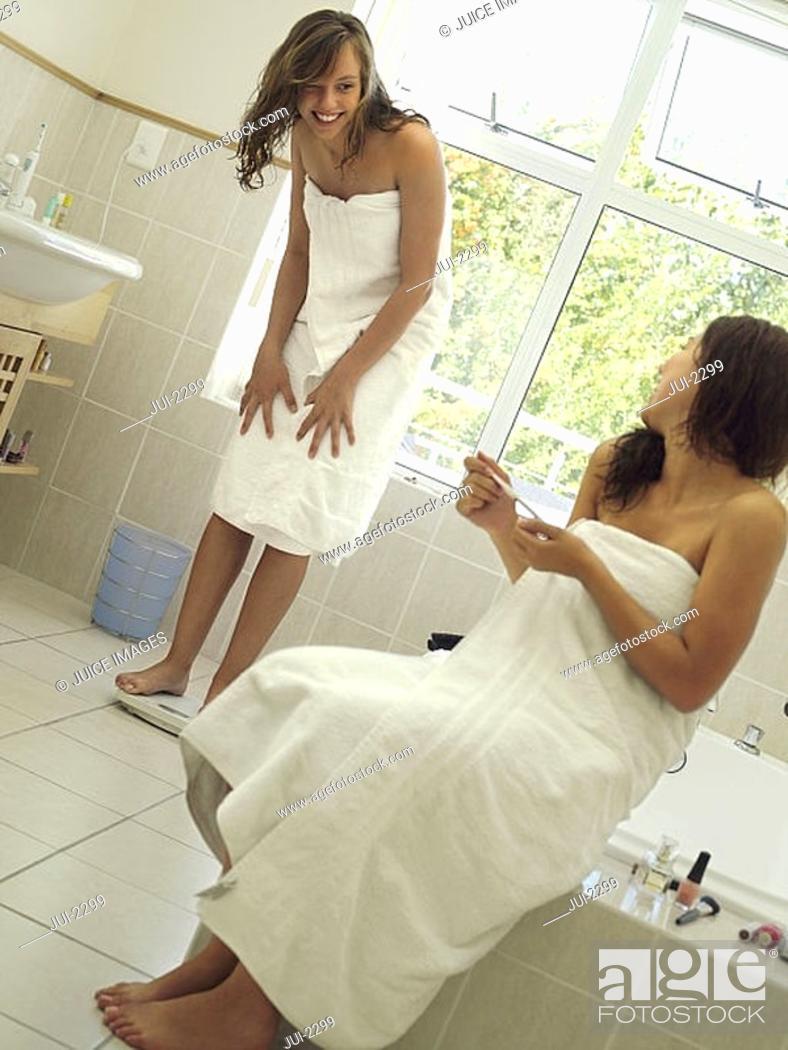 Stock Photo: Teenage girl 15-17 in towel standing on bathroom scales, sister filing nails, smiling tilt.