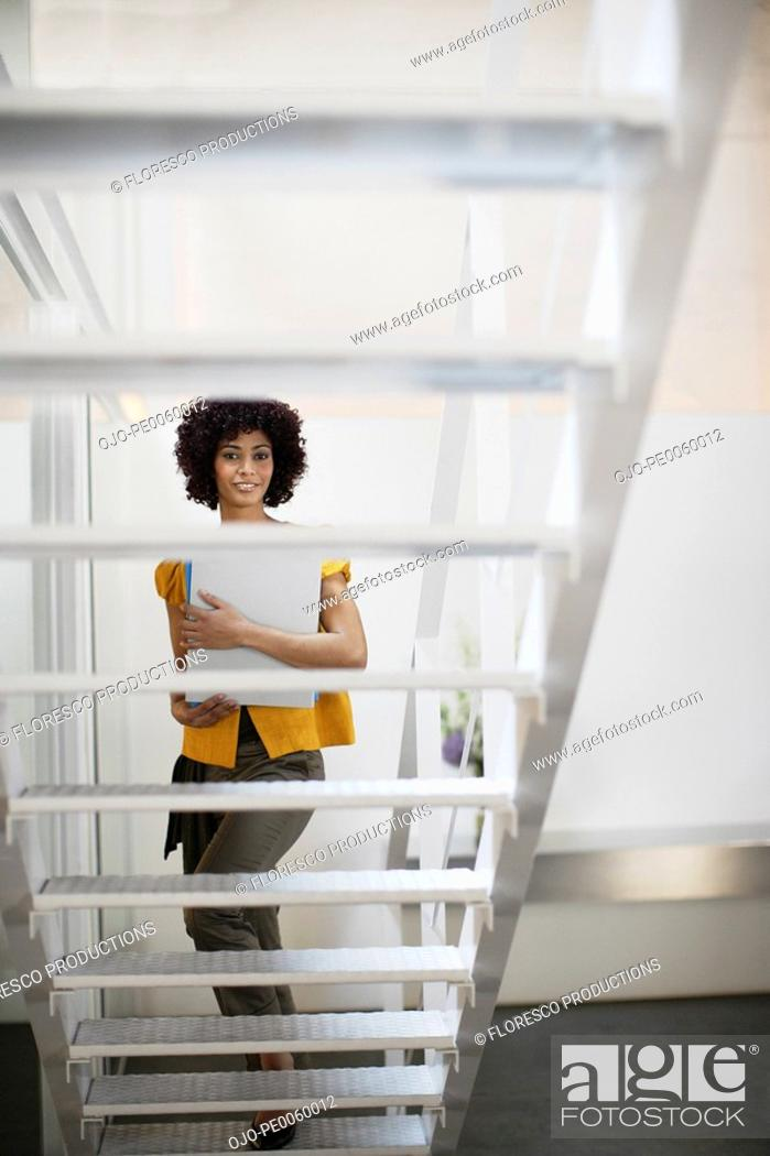 Stock Photo: Businesswoman on office space holding folder at bottom of staircase.