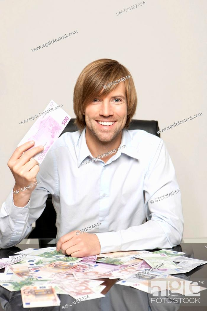 Stock Photo: Happy man at desk with Euro notes.