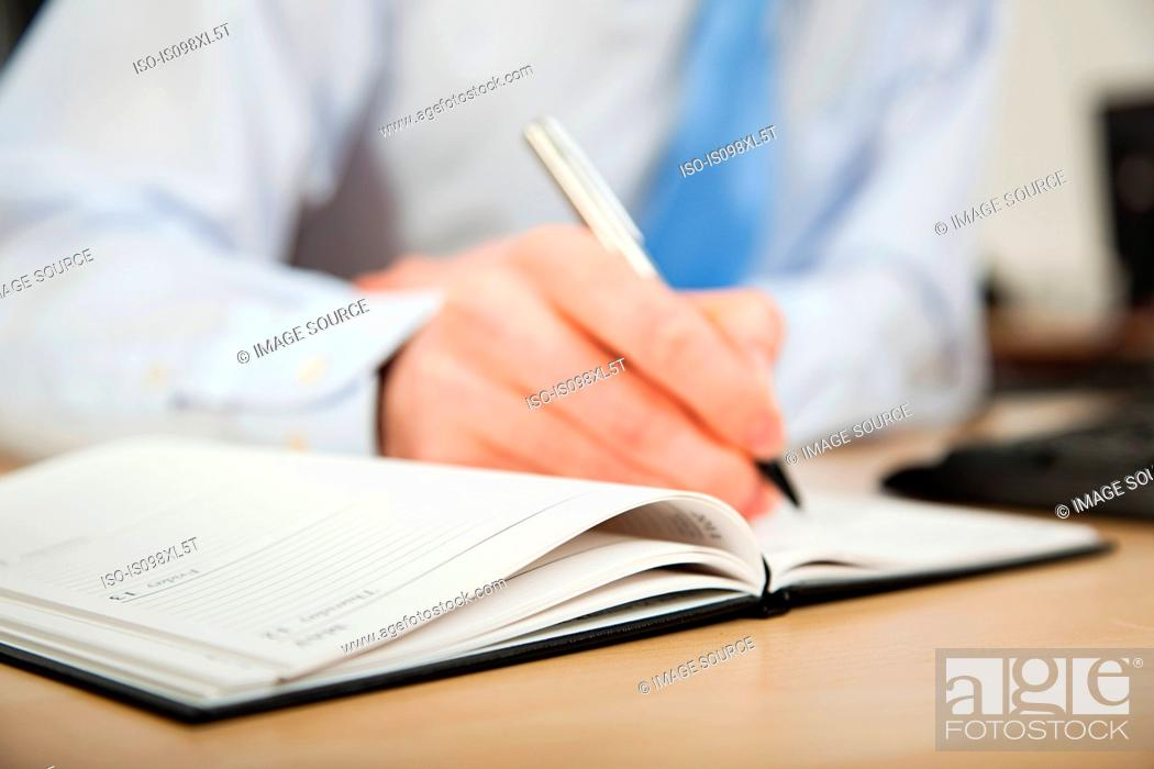 Stock Photo: Office worker writing in diary.