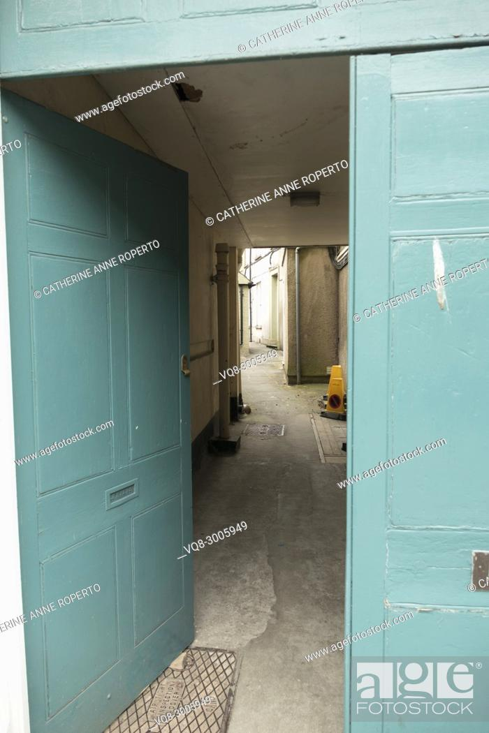 Imagen: Classical teal coloured doorway leading down a grey alley past bright yellow parking cones, Tewkesbury, Gloucestershire, England.