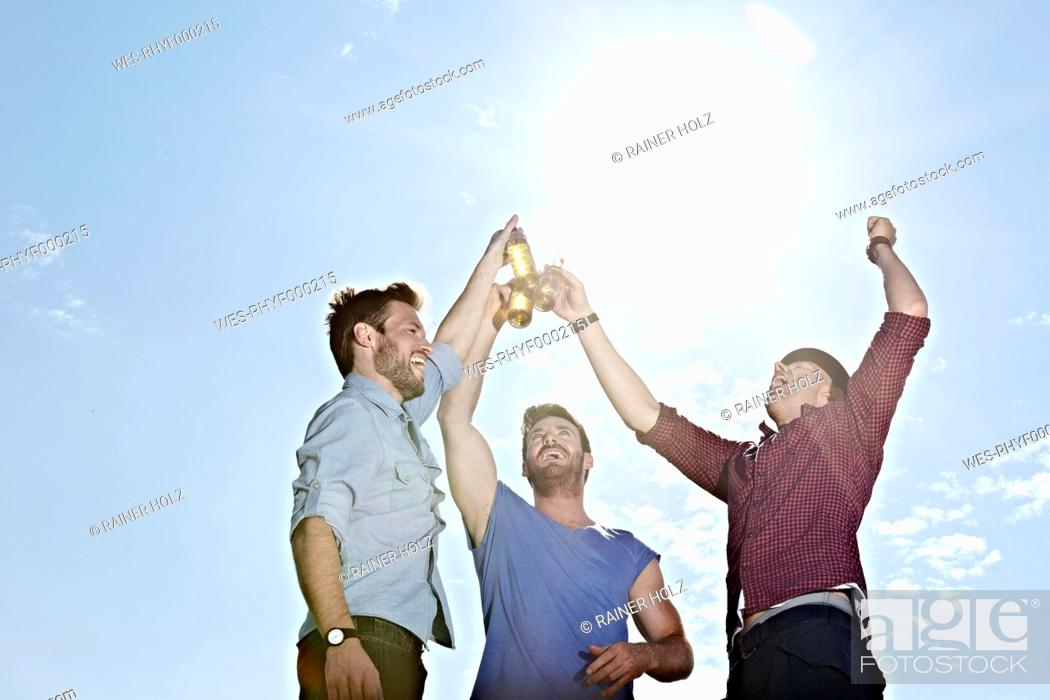 Stock Photo: Germany, Cologne, Young men drinking beer.