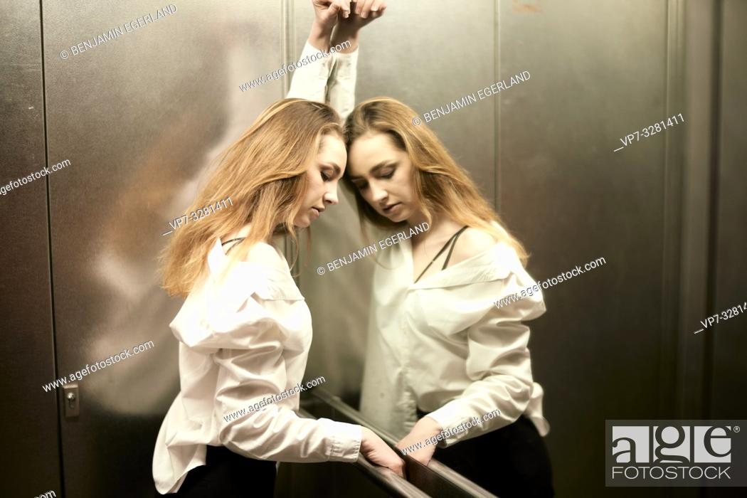 Stock Photo: young woman facing herself in mirror in elevator, tiredness, emotive.