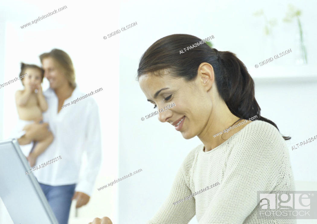 Stock Photo: Young woman looking down at laptop, young man holding little girl in background.