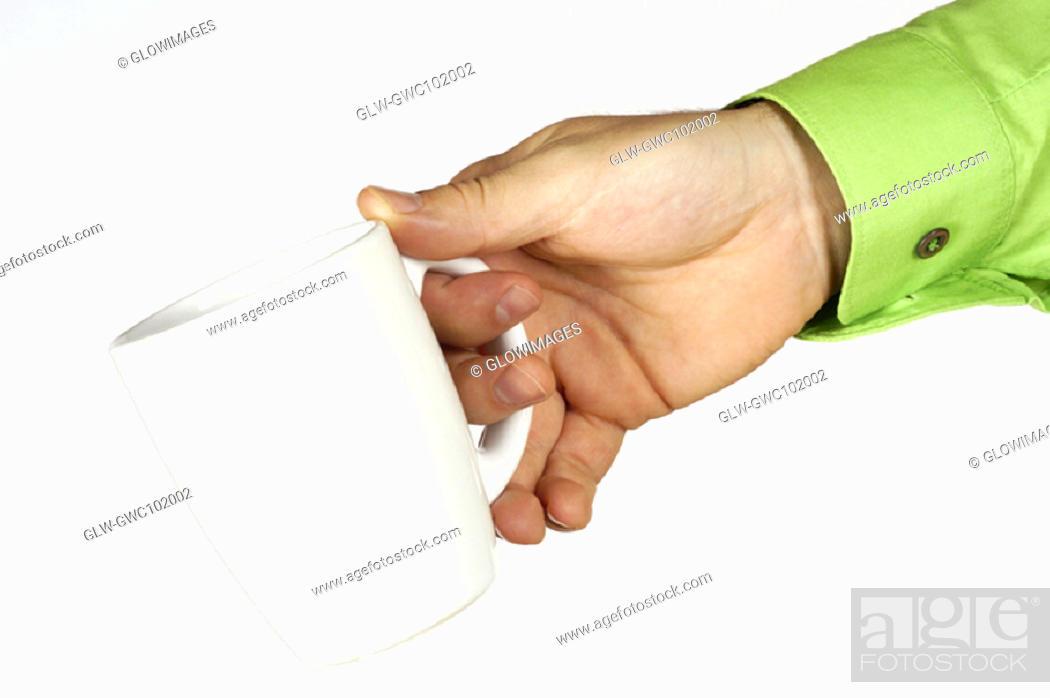 Stock Photo: Close-up of a man's hand holding a mug.