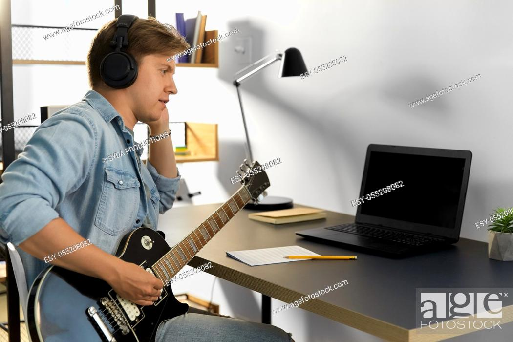 Imagen: man in headphones playing bass guitar at home.