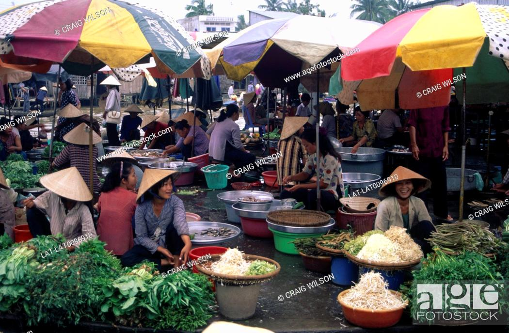 Stock Photo: The busy market place with women at food stalls,with piles of fresh fruit and vegetables,food on display.