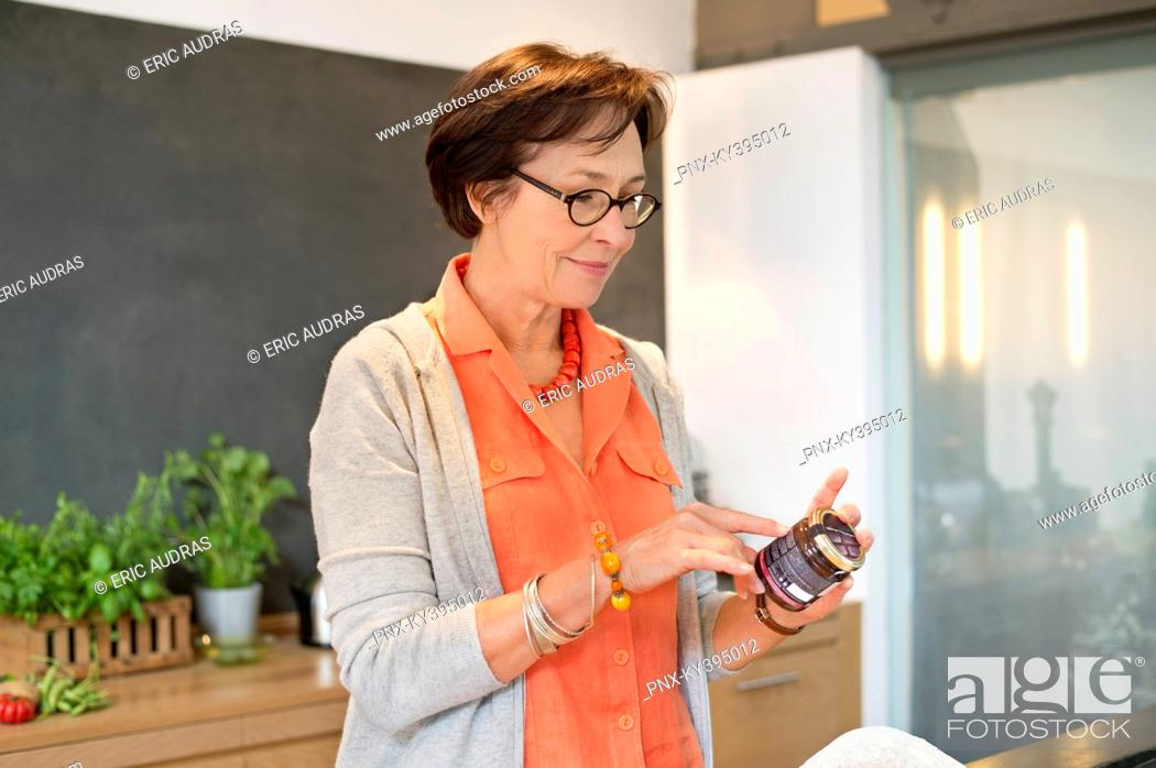 Stock Photo: Woman reading label on a bottle.