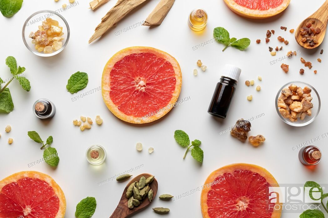 Stock Photo: Bottles of essential oil with fresh grapefruit, peppermint, myrrh, white sandalwood and other ingredients.