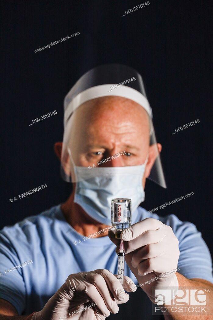 Stock Photo: A male nurse with a dose of Covid-19 vaccine.