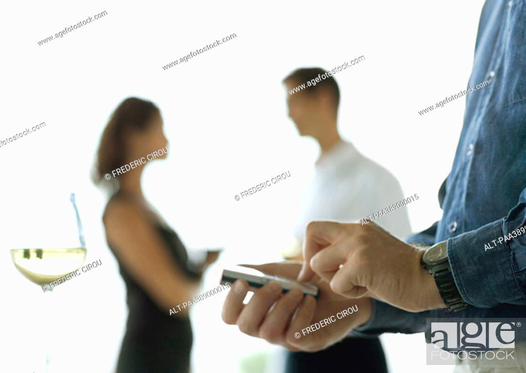 Stock Photo: Man holding cell phone in palm, near glass of wine, people talking in background.