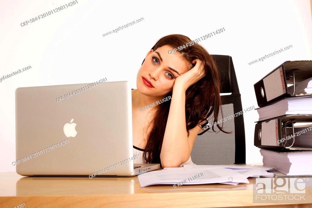 Imagen: A beautiful young woman, lady, girl, secretary, personal assistant, office work, job, employee, worker, computer, notebook, MacBook Pro, paper work, folders.