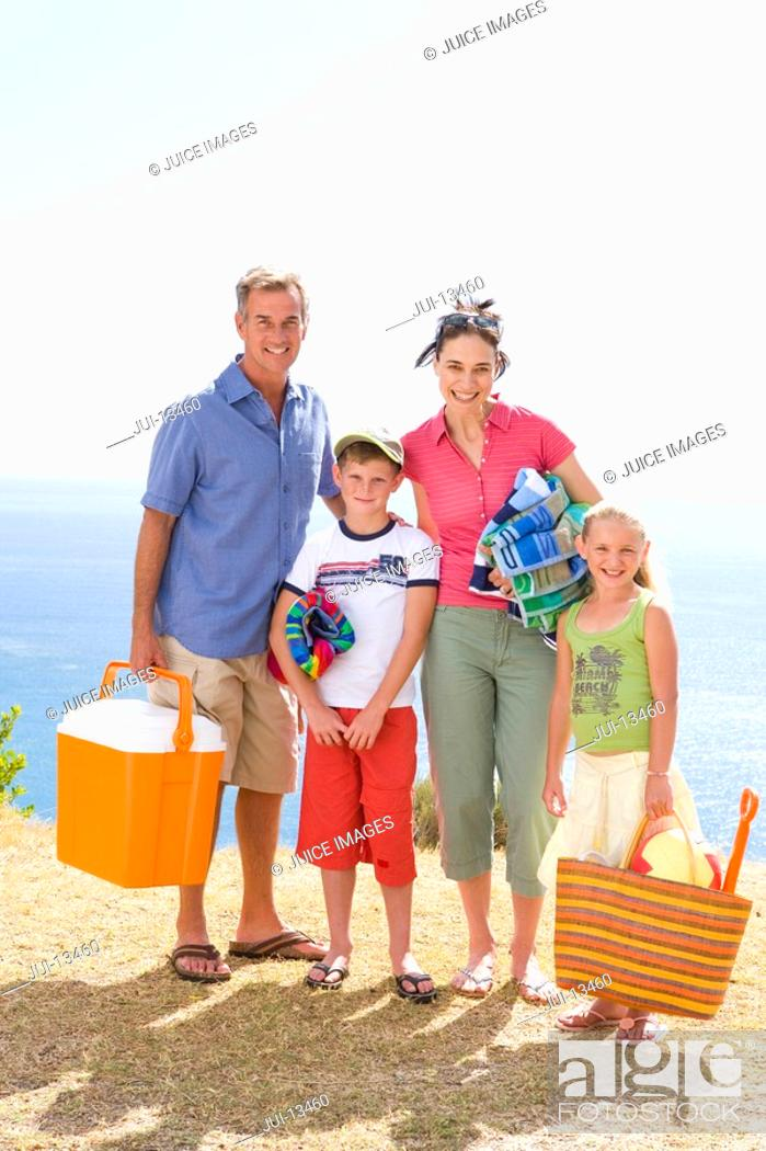 Photo de stock: Family of four with cooler, towels and bag on beach, smiling, portrait.