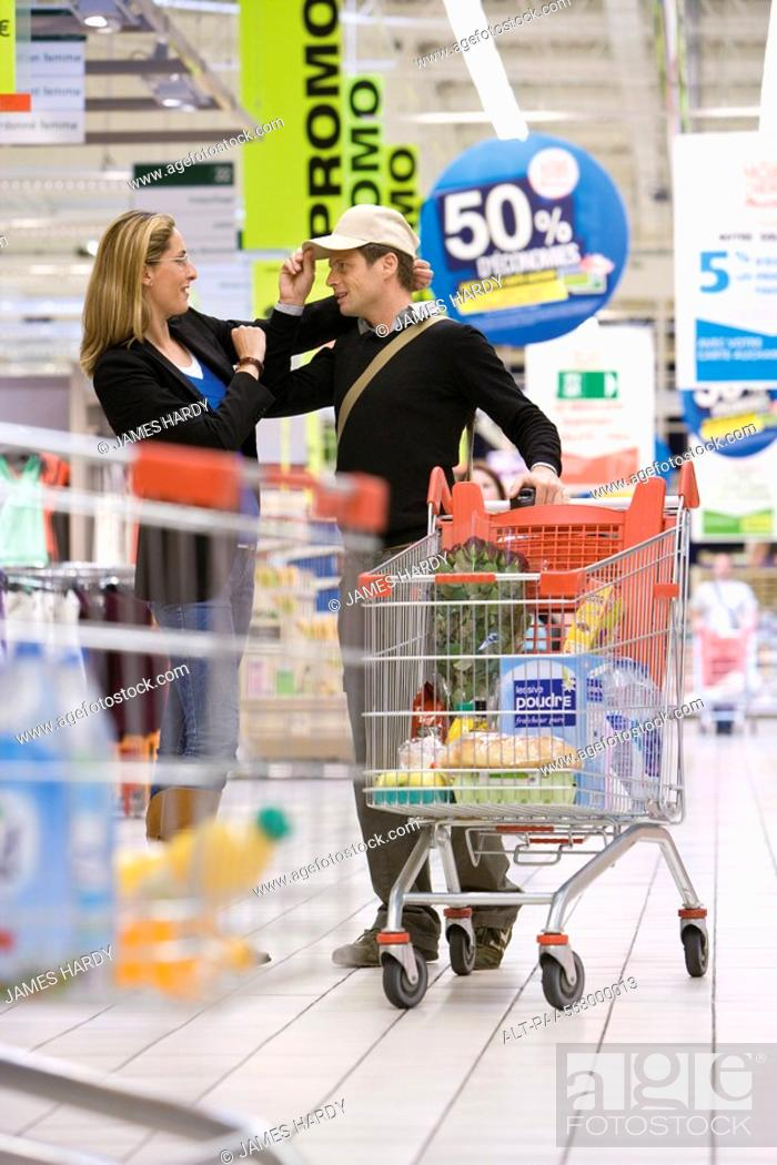 Stock Photo: Couple in supermarket, man trying on hat.
