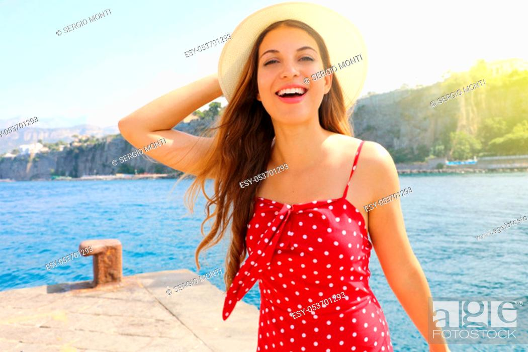 Stock Photo: Smiling attractive fashion girl with red summer dress and hat in Sorrento, Southern Italy.