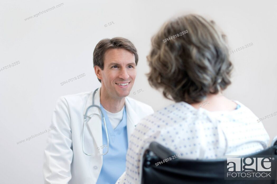 Stock Photo: Male doctor smiling at mature female patient in wheelchair.