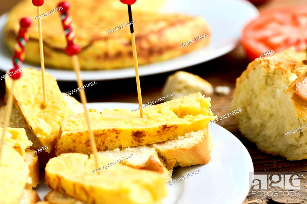 Imagen: closeup of a plate with tortilla de patatas, spanish omelet, served as tapas on sliced bread and a toothpick through it, on a table.