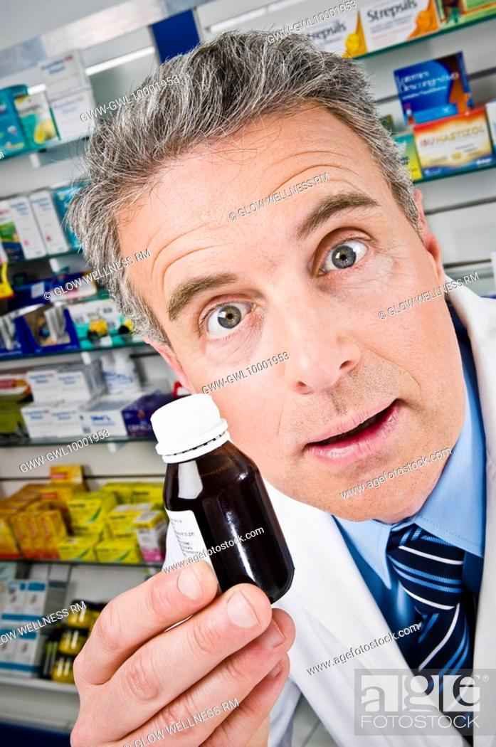 Stock Photo: Pharmacist showing a medicine bottle.