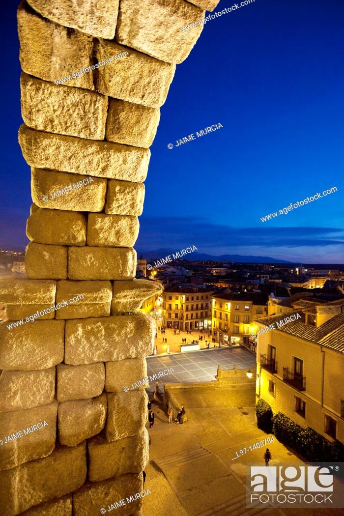 Stock Photo: Night time view of Segovia through the arches of the Aqueduct of Segovia.