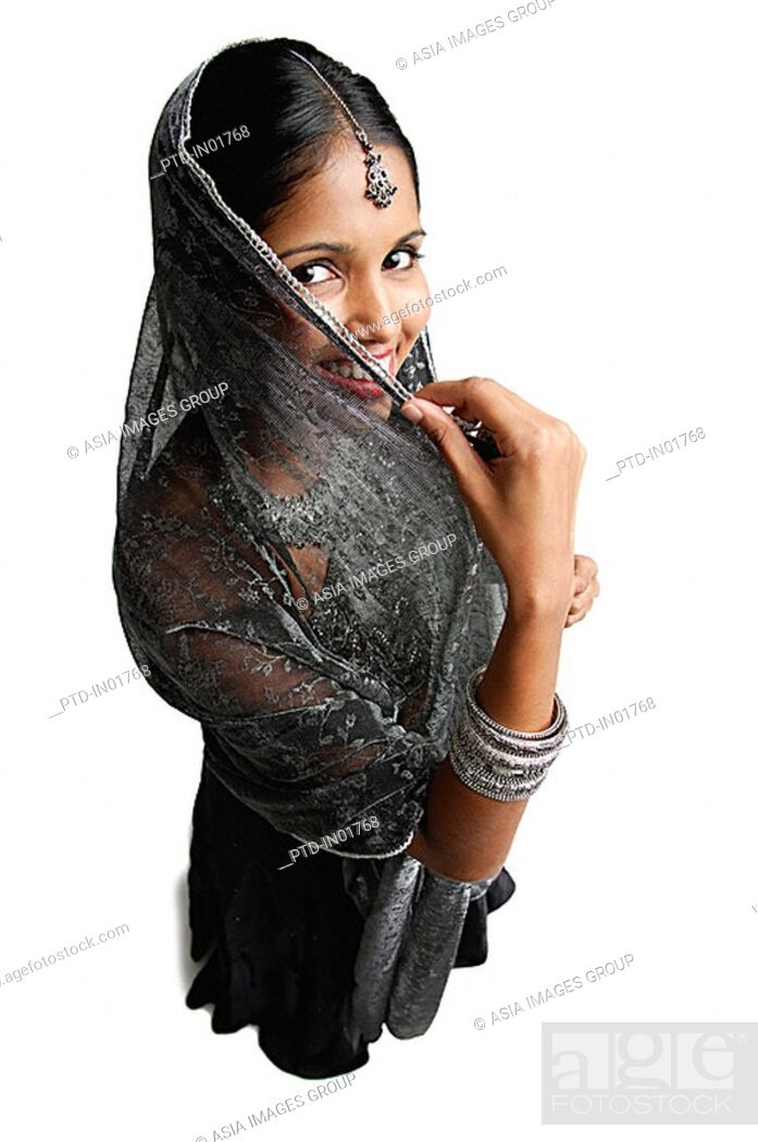 Photo de stock: Woman in gray sari standing against white background, shielding face scarf.